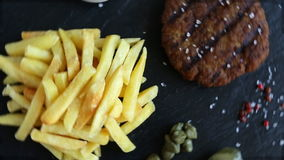 Geroosterde hamburger met frieten en ingelegde komkommersaus stock videobeelden