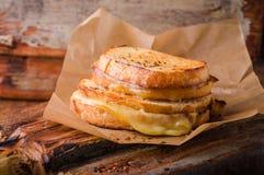 Geroosterde kaassandwich met Spaanse peperpeper op papier op houten raad Selectieve nadruk Stock Fotografie
