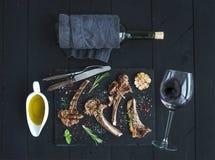 Geroosterde karbonades Rek van Lam met knoflook, rozemarijn, kruiden op leidienblad, wijnglas, olie in een schotel en fles Stock Afbeeldingen