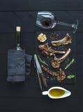 Geroosterde karbonades Rek van Lam met knoflook, rozemarijn, kruiden op leidienblad, wijnglas, olie in een schotel en fles Stock Foto