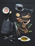 Geroosterde karbonades Rek van Lam met knoflook, rozemarijn, kruiden op leidienblad, wijnglas, olie in een schotel en fles Royalty-vrije Stock Foto