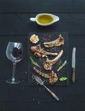 Geroosterde karbonades Rek van Lam met knoflook, rozemarijn, kruiden op leidienblad, wijnglas, olie in een schotel over zwarte Royalty-vrije Stock Afbeelding