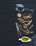 Geroosterde karbonades Rek van Lam met knoflook, rozemarijn, kruiden op leidienblad, wijnglas, olie in een schotel over zwarte Royalty-vrije Stock Foto's