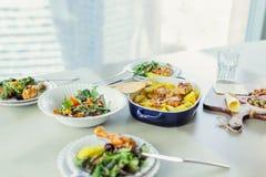 Geroosterde kip met aardappel, groene salades op lijst Stock Foto's