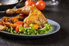 Geroosterde kippenbenen met aardappelwiggen en tomaten Royalty-vrije Stock Foto