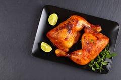 Geroosterde kippenbenen op zwarte plaat Stock Foto