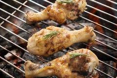 Geroosterde kippentrommelstok over vlammen op een barbecue Stock Foto