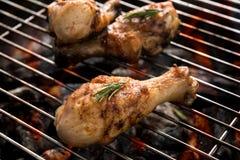 Geroosterde kippentrommelstok over vlammen op een barbecue Royalty-vrije Stock Foto's