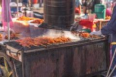 Geroosterde kippenvleespen op de box van het houtskoolvoedsel, straatvoedsel Thailand stock foto's