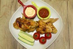 Geroosterde kippenvleugels met groenten en saus op een witte plaat Stock Foto's