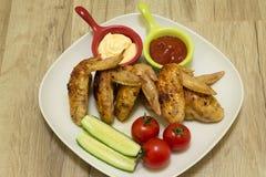 Geroosterde kippenvleugels met groenten en saus op een witte plaat Royalty-vrije Stock Afbeeldingen