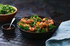 Geroosterde kippenvleugels met wortelen, boerenkool, knoflook en onderdompelende saus in ijzerpan op donkere achtergrond Ruimte v stock foto