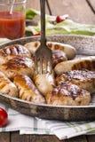 Geroosterde kippenworsten en burgers stock fotografie