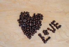Geroosterde koffie die in hart en spelling de woordliefde gestalte wordt gegeven - beeld stock foto's