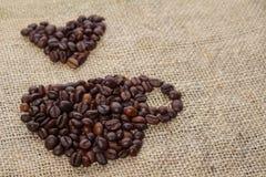 Geroosterde koffiebonen die in de vorm van een kop worden geplaatst Stock Fotografie