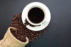 Geroosterde koffiebonen en een kop van koffie op zwarte lijst Stock Foto