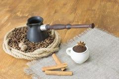 geroosterde koffiebonen en steranijsplant in een ring van hennep, in het centrum van cezve naast een linnenservet met koffiekop e royalty-vrije stock fotografie