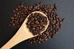 Geroosterde koffiebonen in houten lepels op zwarte lijst Stock Foto