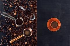Geroosterde koffiebonen, lepel, koffiepot, koffiestamper en kop van koffie op zwarte Royalty-vrije Stock Foto's
