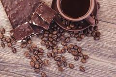 Geroosterde koffiebonen met chocolade en noten op een houten oppervlakte Royalty-vrije Stock Afbeeldingen
