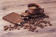 Geroosterde koffiebonen met chocolade en noten op een houten oppervlakte Royalty-vrije Stock Foto's