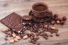 Geroosterde koffiebonen met chocolade en noten op een houten oppervlakte Royalty-vrije Stock Afbeelding