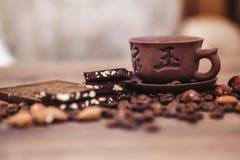 Geroosterde koffiebonen met chocolade en noten op een houten oppervlakte Stock Foto's