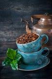 Geroosterde koffiebonen met groene bladeren Stock Fotografie