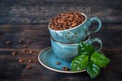 Geroosterde koffiebonen met groene bladeren in koppen Stock Fotografie