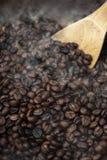 Geroosterde koffiebonen met houten lepel stock afbeelding