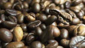 Geroosterde koffiebonen met koffiestof die neer vallen Langzame Motie stock footage