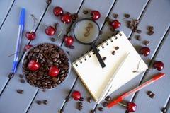 Geroosterde koffiebonen naast rode kersen, blocnote, vulpennen en een vergrootglas op een lichte achtergrond De zomervakantie, stock afbeelding