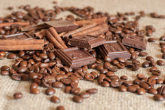 Geroosterde koffiebonen, pijpjes kaneel en stukken van chocolade op een jute Stock Afbeelding