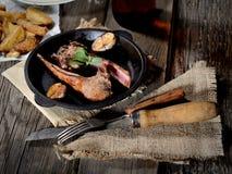 Geroosterde lamskoteletten met knoflook en kruiden in een pan, uitstekende mes en een vork op een servet op een houten achtergron Stock Foto's