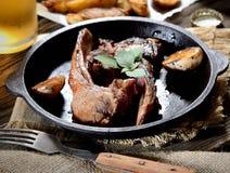 Geroosterde lamskoteletten met knoflook en kruiden in een pan, uitstekende vork, een glas bier op de achtergrond Stock Foto