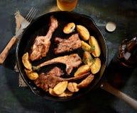 Geroosterde lamskoteletten met kruiden en gebraden aardappels in een pan, uitstekende mes en een vork op een servet op de donkere Stock Afbeeldingen