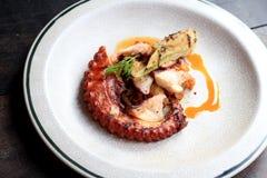 Geroosterde octopustentakels met citroen en peterseliebladeren op schotel royalty-vrije stock afbeeldingen