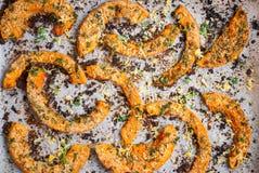 Geroosterde pompoenplakken met kruiden op bakseldocument Royalty-vrije Stock Foto's