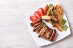 Geroosterde ribben, aardappels en tomaten horizontale hoogste mening Stock Foto