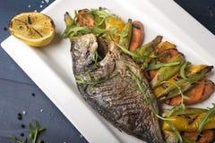 Geroosterde riviervissen op een plaat met citroen en gebakken groenten en arugula stock foto