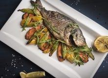 Geroosterde riviervissen op een plaat met citroen en gebakken groenten en arugula royalty-vrije stock foto's