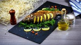 Geroosterde riviervissen op een plaat met citroen en gebakken groenten en peterselie De foto van het voedselrecept, exemplaarteks stock afbeelding
