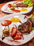 Geroosterde rundvleeslapjes vlees op een plaat met verschillende groenten stock foto's