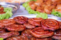Geroosterde of Geroosterde spiraalvormige varkensvleesworsten met rozemarijn, zout en peper op plaat royalty-vrije stock afbeeldingen