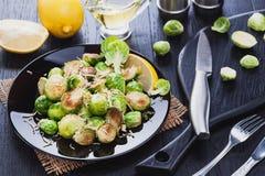 Geroosterde Spruitjes met Parmezaanse kaaskaas, citroen, Zout, Peper op een zwarte lijst Royalty-vrije Stock Foto