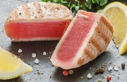 Geroosterde tonijn met peper, citroen en salade Royalty-vrije Stock Foto's