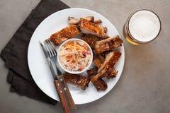 Geroosterde varkensvleesribben in barbecuesaus en honing met zuurkool en bier op een witte plaat Snack aan bier op een lichte ste Royalty-vrije Stock Foto