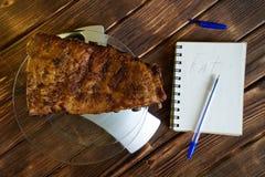 Geroosterde varkensvleesribben in een transparante plaat op een keukenschaal Tellende calorie?n, prote?nen, vetten en koolhydrate stock afbeelding