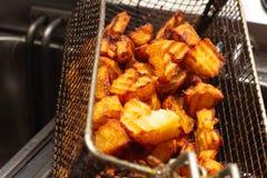 Geroosterde vettige aardappelwiggen in een braadpan, ongezonde kost, cholesterol stock foto