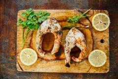 Geroosterde vissen met citroen en peterselie stock afbeeldingen
